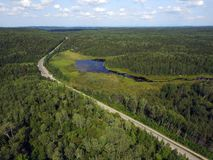 Aerial view of road in forest with bog. Aerial view of a road going through forest and mountains with bog or marsh, Quebec, Canada stock photos