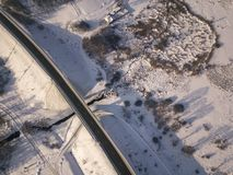 Aerial view on road and forest landscape in winter season royalty free stock photos