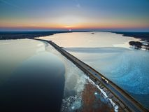 Aerial view of road in the frozen lake with moving cars on sunset, winter view stock photos