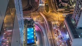 Aerial view of a road intersection in a big city night timelapse. Urban landscape of Dubai Marina district in UAE with cars and skyscrapers and tram line stock video