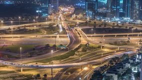 Aerial view of a road intersection in a big city night timelapse. Urban landscape of Dubai Marina district in UAE with cars and skyscrapers and metro line stock footage