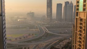 Aerial view of a road intersection in a big city at sunrise timelapse. Urban landscape of Dubai Marina district in UAE with cars and skyscrapers stock footage