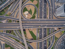 Aerial view of road junction with railway tracks in Dubai, UAE. On the road going trucks, cars, trains Stock Photos