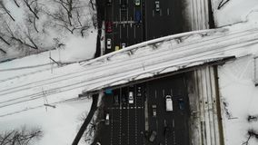 Aerial view of road junction winter time with cars, busses, and other traffic with railway bridge above road. stock footage