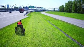 Aerial view of Road landscaper cutting grass along the modern highway stock video