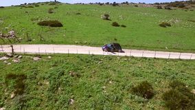 Aerial View Of The Road With Parked Car. Drone camera flies over the hilly road with parked cabriolet while woman walking away from the parked car on the stock video