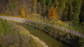 Aerial view of the road and the river near the autumn forest stock video footage