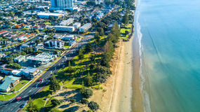 Aerial view on a road running along sea shore with residential suburbs on the background. Auckland, New Zealand. Royalty Free Stock Photo
