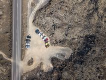 Aerial view of a road that runs through lava fields and cars parked. Lanzarote. Spain. Aerial view of a road that runs through lava fields and cars parked royalty free stock images