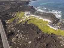 Aerial view of a road that runs through lava fields between the indented coastline of Lanzarote. Spain. Aerial view of a road that runs through lava fields stock photo
