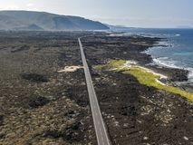 Aerial view of a road that runs through lava fields between the indented coastline of Lanzarote. Spain. Aerial view of a road that runs through lava fields stock photography