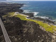Aerial view of a road that runs through lava fields of Lanzarote. Spain. Aerial view of a road that runs through lava fields between the indented coastline of royalty free stock image