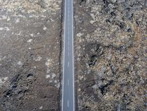 Aerial view of a road that runs through lava fields of Lanzarote. Spain. Aerial view of a road that runs through lava fields between the indented coastline of stock image