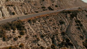 Aerial view on the road with two cars. Beautiful view on the road with car and two people inside it. The car is driving on the long road between the rocks. The stock video