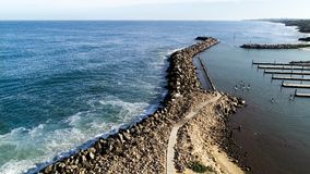 Aerial view of rock sea wall boat harbour with stand up paddle boarders near piers. Aerial view of rock sea wall boat harbour with stand up paddle boarders in royalty free stock images