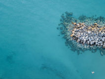 Aerial view of rocks on the sea, and two swimmers floating Royalty Free Stock Image