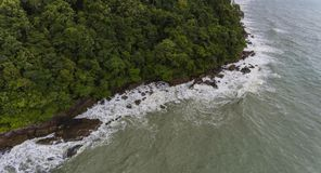 Aerial view of a rocky and beach shore. Koh Chang, Thailand. Aerial view of a rocky and green beach shore. Waves crashing on the rocks next to the lush trees stock images