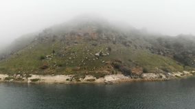 Aerial view of a rocky coast. Mountain turquoise lake among the hills in cloudy weather and fog. Landscapes of the North. Caucasus stock video footage