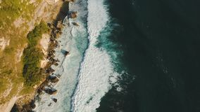 Rocky coastline on the island of Bali. Aerial view. Aerial view of rocky coast with surf the waves off the at sunset, Bali,Indonesia, Pura Uluwatu cliff. Waves stock video footage