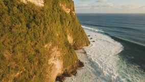 Rocky coastline on the island of Bali. Aerial view. Aerial view of rocky coast with surf the waves off the at sunset, Bali,Indonesia, Pura Uluwatu cliff. Waves stock footage