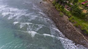 Aerial view of a rocky and green beach shore. Waves crashing on the rocks next to the lush trees. Koh Chang, Thailand stock images