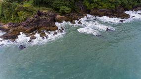 Aerial view of a rocky and green beach shore. Waves crashing on the rocks next to the lush trees. Koh Chang, Thailand royalty free stock photo