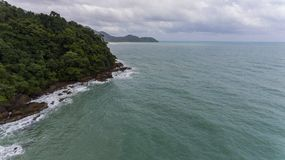 Aerial view of a rocky and green beach shore. Waves crashing on the rocks next to the lush trees. Koh Chang, Thailand royalty free stock photography