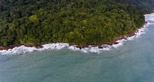 Aerial view of a rocky and green beach shore with amazing blue water. Waves crashing on the rocks next to the lush trees. Koh Chang, Thailand royalty free stock photos