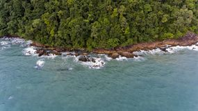 Aerial view of a rocky and green beach shore with blue water. Aerial view of a rocky and green beach shore with amazing blue water. Waves crashing on the rocks stock photos