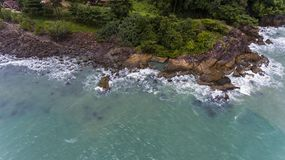 Aerial view of a rocky and green beach shore. Waves crashing on the rocks next to the lush trees. Koh Chang, Thailand royalty free stock photos