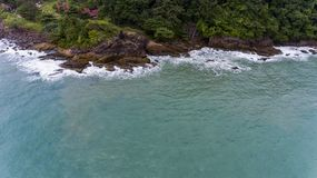 Aerial view of a rocky and green beach shore. Waves crashing on the rocks next to the lush trees. Koh Chang, Thailand royalty free stock images