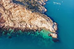 Aerial view of rocky island and azure ocean water from air, beautiful travel nature landscape.  royalty free stock images