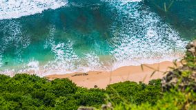 Aerial view of rolling turquoise ocean waves over pure clear sandy beach on sunny day. Surrounded by lush green jungle Stock Photo