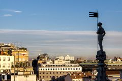 Aerial view from the roof of the cathedral of Milan. One of numerous statues of main Cathedral in Milan looks on modern city, Ital. Numerous statues on steeples Stock Photography