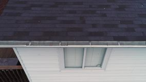 Aerial view roof inspector examining house gutters. A simulated drone video feed of a roof inspector examining a home's shingles and gutters stock video footage