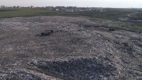 Aerial view of rubbish dump, people work at landfill near trucks, seagulls fly over large garbage pile stock video
