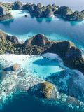 Aerial View of Rugged Limestone Islands in Wayag, Raja Ampat. The amazing limestone islands found in Wayag, Raja Ampat, Indonesia, are surrounded by healthy stock photography