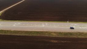 Aerial view of a rural asphalt motorway. Cars are moving along the highway. Cars and trucks drive along a country road. Highway road air footage. Plowed fields stock video