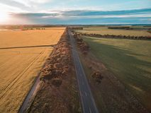 Aerial view of rural road passing through agricultural land in Australian countryside at sunset. Royalty Free Stock Photo