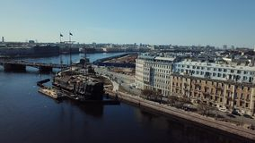 Aerial view of Russian cruiser Aurora near the bridge in Saint-Petersburg against blue sky. Stock footage. Petersburg. Aerial view of Russian cruiser Aurora near stock video footage