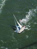 Aerial view of sailboat swiftly racing under the Golden Gate Bridge on a sunny day Stock Photo
