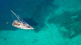 Aerial view of sailing boat anchoring on coral reef stock photography