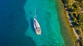 Aerial view of sailing boat anchoring next to reef royalty free stock images