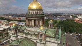 Aerial view of Saint Isaac`s Cathedral an downtown of St.Petersburg Russia. Golden domes. Angels. Dramatic sky. Close approach stock video