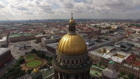 Aerial view of Saint Isaac`s Cathedral an downtown of St.Petersburg Russia. Golden domes. Angels. Dramatic sky. Close approach stock footage