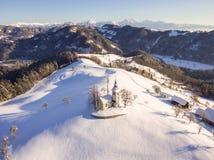 Aerial view of Saint Tomas church in winter, Slovenia. stock photos