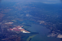 Aerial view of salt evaporation ponds, bridge, airports, cities Royalty Free Stock Images