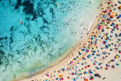 Aerial view of sandy beach with umbrellas and sea. Aerial view of sandy beach with colorful umbrellas, swimming people in sea bay with transparent blue water in stock image