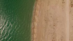 AERIAL VIEW. Sandy Beach In Crimea. AERIAL VIEW. The shot is divided into two parts - sandy beach on the right and emerald rippled water of the sea with stock video