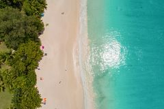 Aerial view of sandy beach with tourists swimming in beautiful clear sea water.  stock images